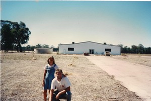 Andrew with daughter Amy stand in front of a bare paddock with the plain white shed that would become Warrabilla. Circa 1996